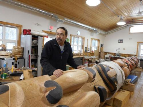 Artist Keith Wolfe Smarch displays the Learning Center totem in the carving shed.  The goal of the carving shed is to preserve and carry on Carcross/Tagish First Nation stories and culture as well as teach people traditional skills. (Photo: Samantha Dawson)